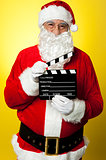 Cheerful Kris Kringle posing with clapperboard