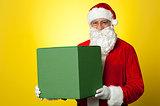 Santa Claus delivering big green gift box