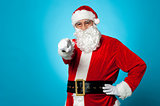 Handsome man in Santa costume pointing at you
