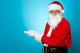 Santa against blue background posing with open palms