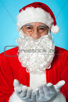 Smiling aged Santa posing with open palms