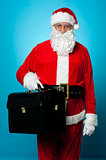 Santa is all set to visit his new office, holding briefcase