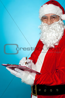 Santa Claus making notes in the wish list
