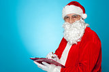 A thoroughly modern Santa claus checks his list on clipboard