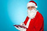 A thoroughly modern Santa claus checks his list on clipboard