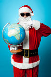 Stylish Santa in dark shades pointing at the globe