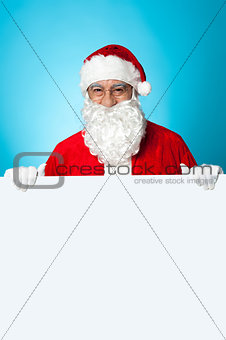 Aged Santa standing behind a blank ad board