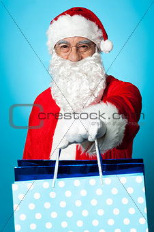 Santa holding shopping bags in his outstretched arms