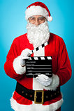 Bespectacled Santa holding a clapperboard