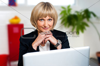 Business executive posing with laptop open at work desk