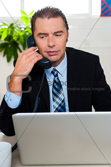 Man in formal attire talking on the phone