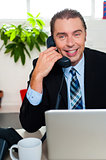 Smiling male manager attending clients call