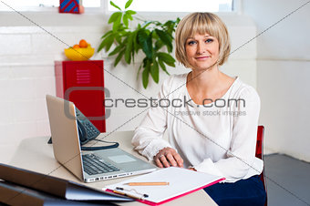 Casual portrait of a woman seated at her work place