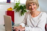Blonde woman facing camera while working on laptop