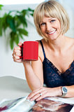 Portrait of a relaxed woman holding red coffee mug