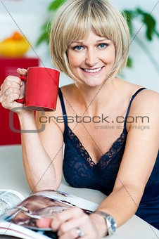 Attractive woman enjoying coffee and reading magazine