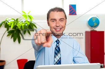Businessman at work desk pointing at you