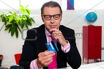Corporate man staring at his credit card