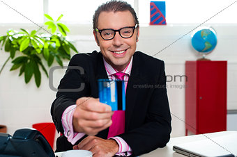 Smiling business executive displaying credit card