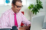 Busy employee in office working on laptop