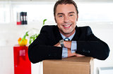 Handsome businessman leaning on packed carton
