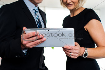 Business colleagues watching videos on tablet