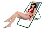 Glamorous bikini model relaxing on reclining chair