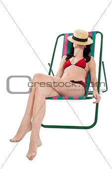 Slim woman relaxing. Face covered with hat.