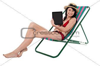 Smiling bikini model promoting tablet pc