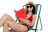 Enticing bikini model on a deckchair reading a book