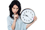 Young brunette with wall clock gesturing silence
