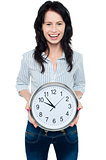 Cheerful brunette in casual presenting a wall clock
