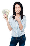 Pretty woman holding up fan of dollar notes