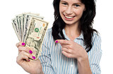 Happy woman holdng and pointing towards dollar notes