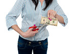Woman cutting ten dollar banknote with scissors