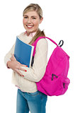 Joyful college student posing with pink backpack