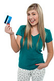 Joyous teenager displaying credit card