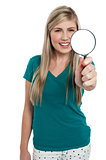 Attractive girl holding magnifying glass