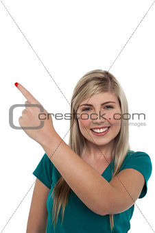 Blonde girl pointing away on white background