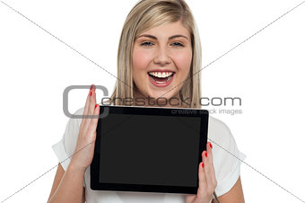 Active caucasian girl displaying tablet device