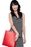 Joyous brunette posing with red shopping bag