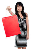 Smiling woman offering bag full of gifts