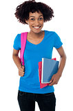 College student carrying back pack, book and clipboard