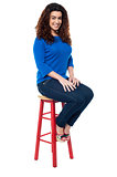 Long curly haired lady seated on red stool