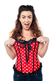 Excited woman adjusting her polka dotted corset top