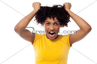 Angry young woman pulling her hair out