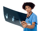 Young serious lady surgeon holding x-ray sheet