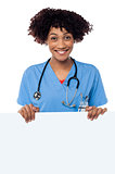 Joyous female doctor standing behind ad board