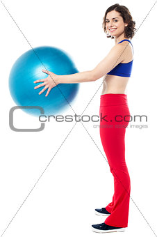 Fit woman posing with big blue exercising ball