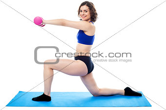 Fit lady with dumbbells kneeling on one leg